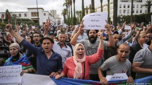 """Protesters take part in a march on 27 June 2018 denouncing heavy sentences against Hirak activists in Rabat, Morocco. Banner in Arabic reads """"Moroccan Justice. Life sentence for the (northern region of) of Rif. A noose for the country"""" (photo: picture alliance/AP/M. Elshamy)"""