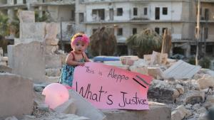 "Sama standing on ruins in Aleppo in 2016. She holds a placard which says ""This is Aleppo. What's justice?"" (source: ""For Sama""/Waad al-Kateab)"