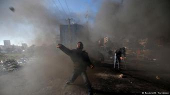 "Clashes with police: a Palestinian protester hurls stones toward Israeli police during clashes near the Jewish settlement of Beit Al, close to the West Bank city of Ramallah. Palestinians called for a ""day of rage"" in response to U.S. President Donald Trump′s decision to recognise Jerusalem as Israel's capital. At least two protesters were killed on Friday during clashes with security forces"