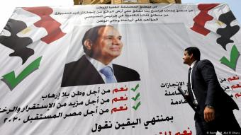 "A man walks in front of a banner reading, ""Yes to the constitutional amendments, for a better future"", with a photo of Egyptian President Abdul Fattah al-Sisi before the approaching referendum on constitutional amendments in Cairo, 16 April 2019 (photo: Reuters/M. Abd El Ghany)"